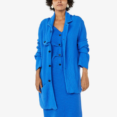 Blue jacket with irregular front button fastening with one front pocket and an asymmetrical hemline.