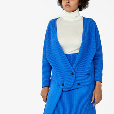 Wrap blue bomber is made of a wrinkled effect cotton knit and features adjustable button fastening at the front.
