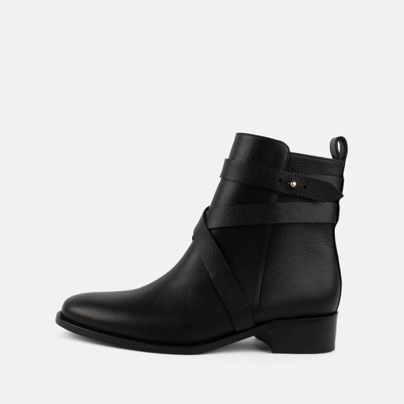 Black ankle leather boots with side zipper with straps around the ankle.