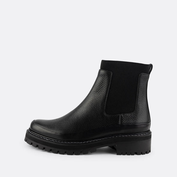 Black leather chelsea boots with rubber outsole.