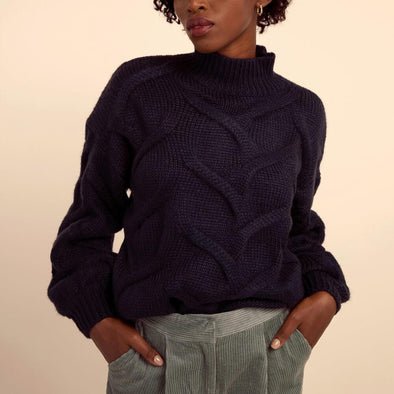 Navy blue soft sweater featuring a high collar and low shoulders.