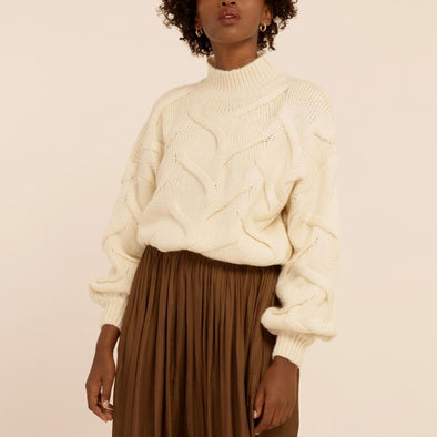 White soft sweater featuring a high collar and low shoulders.