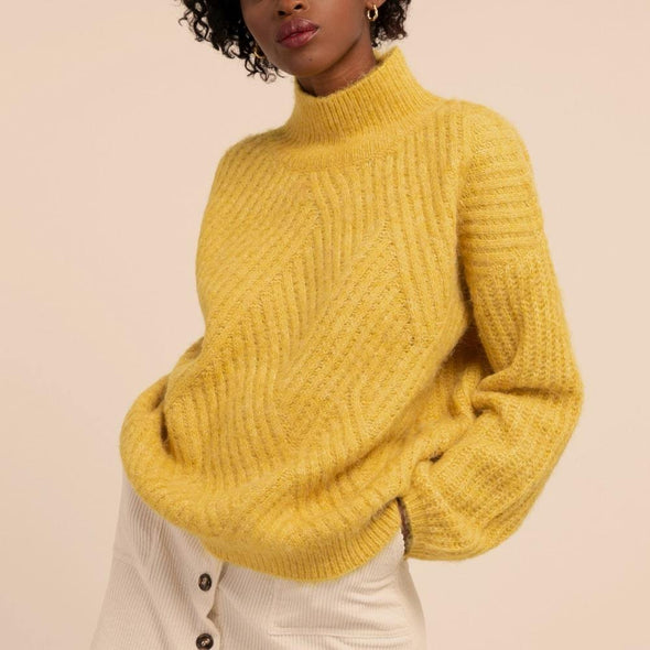 Yellow fluffy knit featuring a hogh collar and low shoulders.