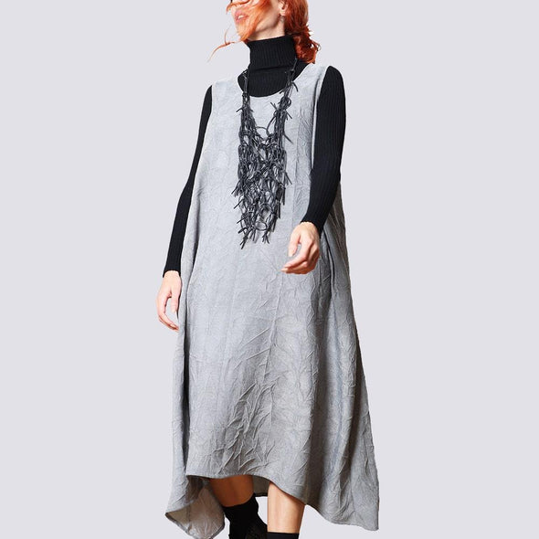 Round sleeveless crinkled fluid grey dress with A-line fit maxi length seam pockets and round collar.