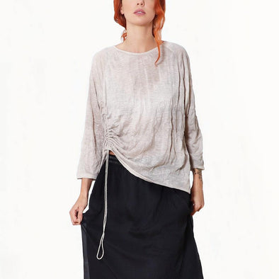 Asymmetrical crinkled beige jersey top with ong sleeves and drawstring on the front side.