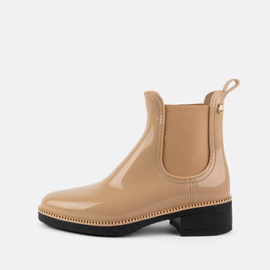 Glossy beige chelsea rain boots in non-toxic PVC.