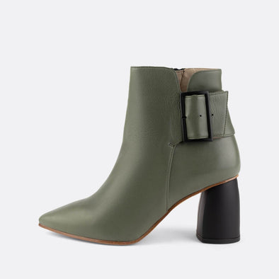 Pointed toe green leather ankle boot with oversized buckle and square heel.