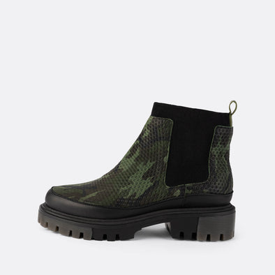Chelsea boots with green camouflage material and chunky black sole.
