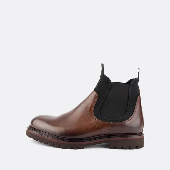 Brown leather chelsea boots with black elastic detail.