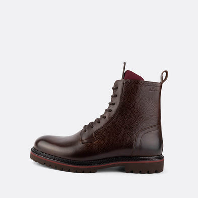 Lace-up brown leather boots with red deatil on the sole and the tongue.
