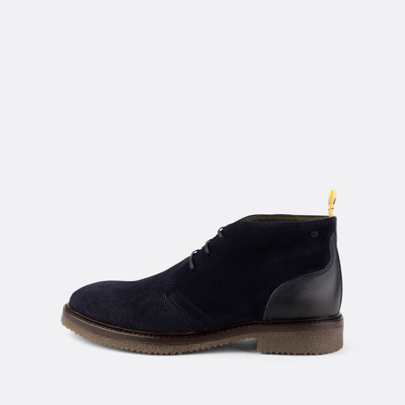 Navy blue desert boots with brown rubber sole and yellow detail on the ankle.