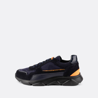 Black and navy sneakers with chunky black sole and orange details.