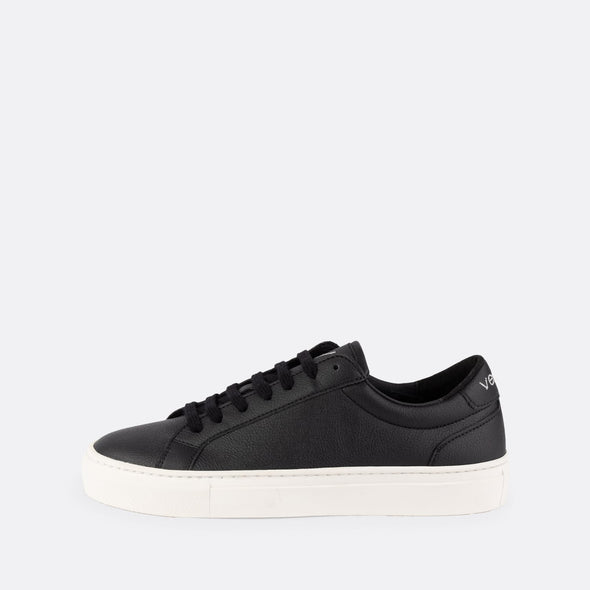 Minimalistic low top black sneakears with white sole and brand logo on the ankle.