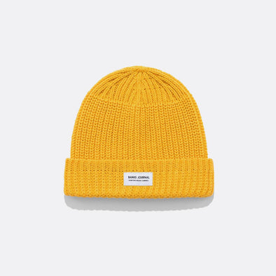 Yellow beanie in mixed knit texture and recycled polyester woven labels.