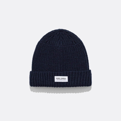 Navy blue beanie in mixed knit texture and recycled polyester woven labels.