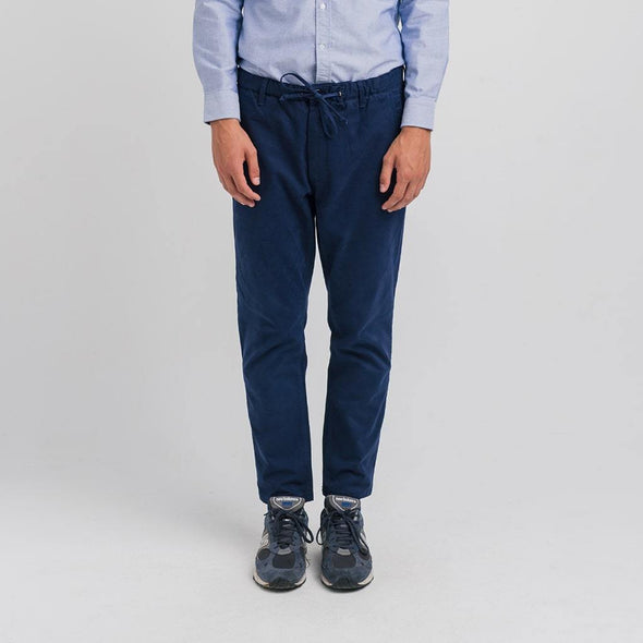 Loose fit blue trousers with elastic waistband with drawstring for ease.
