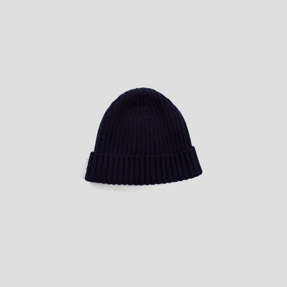 Rib knit navy beanie tube-knitted from wool yarn.