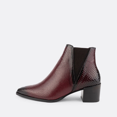 Heeled ankle boot made of leather with pointed toe and engraved snake effect.