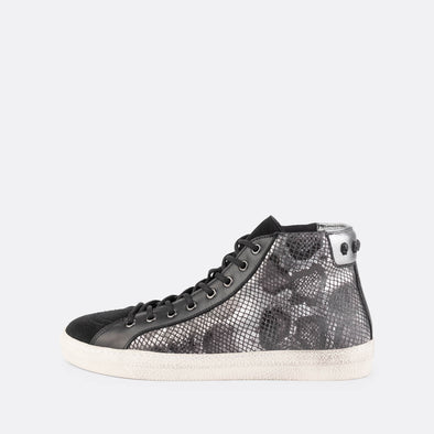 Low top snake pattern sneakers with skull details on the ankle and black suede on the front.
