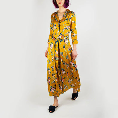 Yellow floral long dress with a tuxedo neckline and belt at the waist.