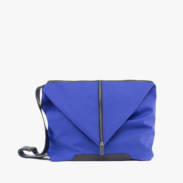 Amorphous bag composed of two panels: black full grain leather and soft rubber in snorkel blue, closes with silver zipper
