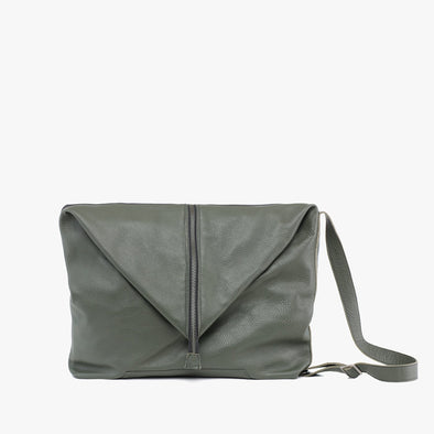Amorphous bag composed of two panels: army green full grain leather and soft rubber in black, closes with silver zipper