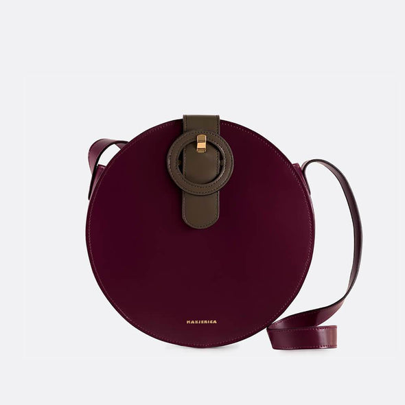 Burgundy and olive green round leather shoulder bag with the brand's signature buckle.