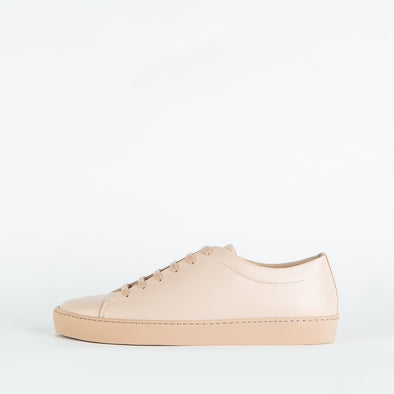 Nude full grain Italian leather sneakers paired with a stitched plain rubber cup sole and cotton laces.