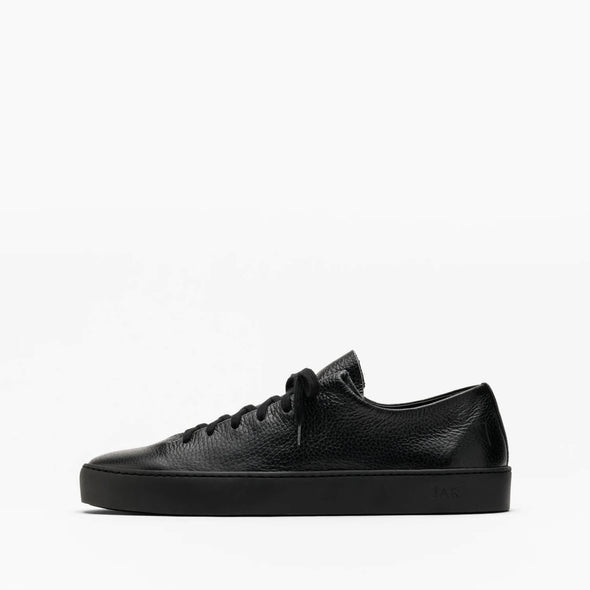 One piece black leather sneakers with a stitched plain rubber cup sole.
