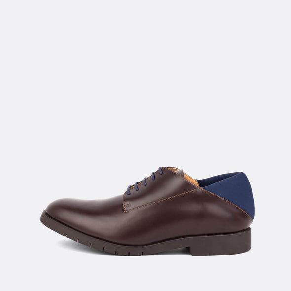 Brown leather derby shoes with a navy blue neoprene heel.