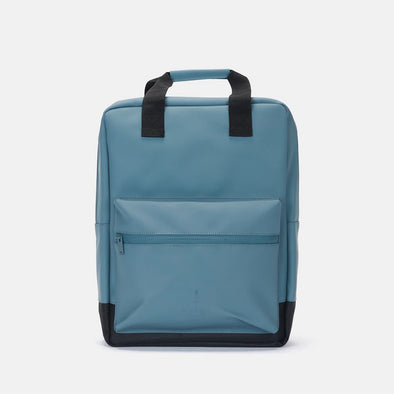 Minimalist boxy backpack in blue synthetic with front pocket, matching zippers and handle