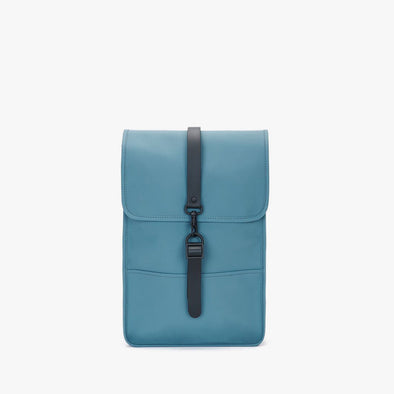 Boxy minimalist backpack in turquoise blue synthetic with a single metallic black hook clasp