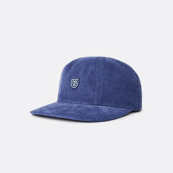 "Blue six-panel cotton twill cut-and-sew cap featuring an embroidered """"B"""" shield patch and a leather strap."