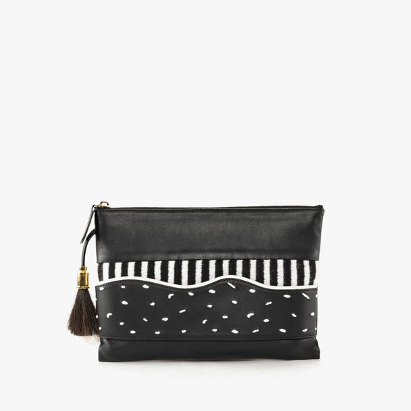 Thin leather pouch with textile appliques in black and white with top zipper and black tassel