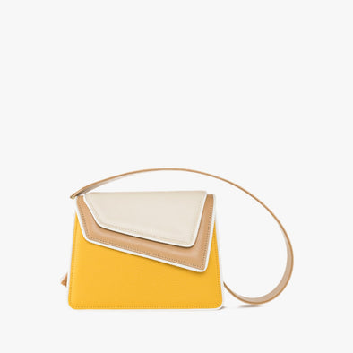 Shoulder bag in a color block combination of beige and yellow leather with asymmetrical flap and thick detachable beige leather strap with embroidered details