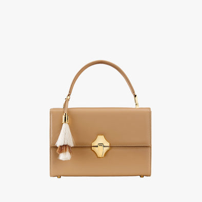 Boxy bag in orange leather with golden metallic clasp, handle and detachable shoulder strap, white and beige interchangeable tassel
