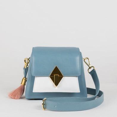Geometrical structured retro-stylebag in soft blue with white and soft pink panels, golden metallic hardware, detachable shoulder straps and horse mane tassel