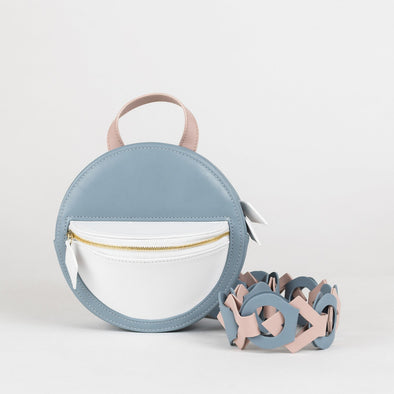 Small circular-shaped backpack in soft blue leather with white panel and pastel pink handle with detachable straps and horse mane tassel