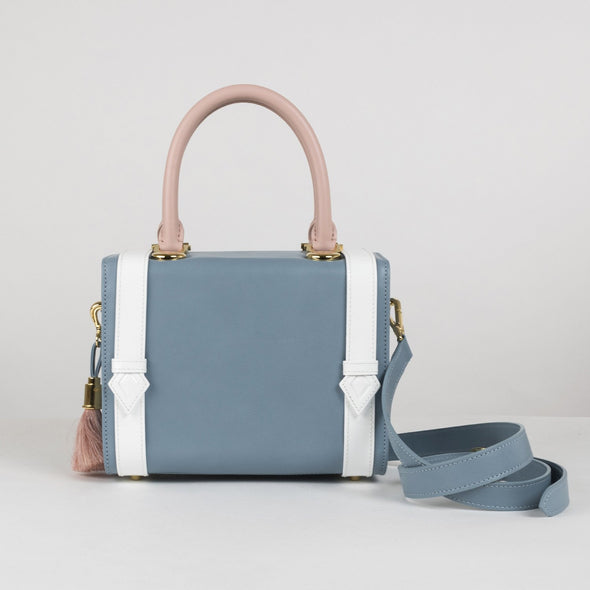 Geometrical structured box bag in soft blue leather with white embellishing buckle straps and pastel pink handle with detachable shoulder strap