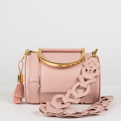 Geometrical structured cylindrical satchel bag in blush pink leather with golden metallic handle and detachable shoulder strap