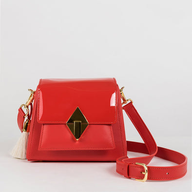 Geometrical structured retro-stylebag in red leather with patent leather flap, golden metallic hardware, detachable shoulder straps and horse mane tassel