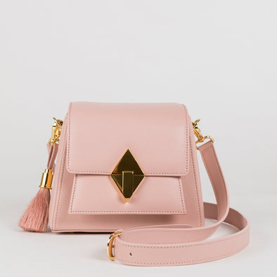 Geometrical structured retro-stylebag in pastel pink leather, golden metallic hardware, detachable shoulder straps and horse mane tassel