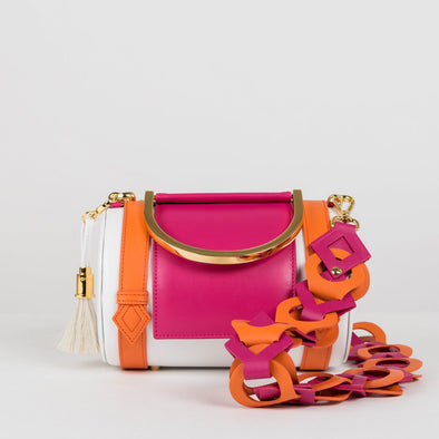 Geometrical structured cylindrical satchel bag in white leather with orange and fuchsia pink details, golden metallic handle and detachable shoulder strap