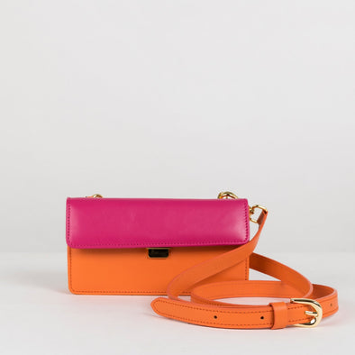 Rectangular small case in orange leather with fuchsia pink flap, detachable pink wrist strap and orange shoulder strap