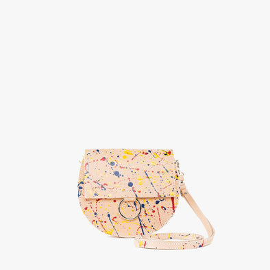 Round minimalist shoulder bag in natural color leather handpainted in a splatter-style in red, yellow and blue with silver hoop embellishment on the flap and detachable strap
