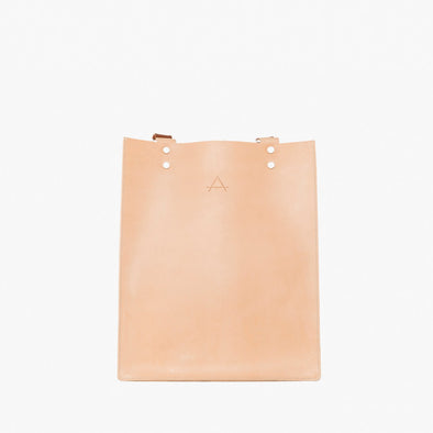 Rectangular minimalist backpack/totebag in natural chemical-free leather with camel strap that can be adjusted through the silver hoops to be worn on the shoulder or as a backpack