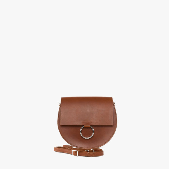 Round minimalist shoulder bag in camel chemical-free leather with silver hoop embellishment on the flap and detachable strap