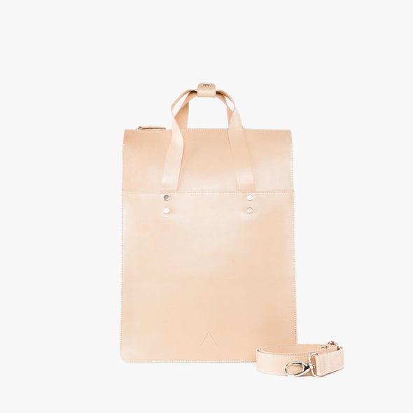Rectangular minimalist backpack/totebag in natural chemical-free leather with handle held by two silver metallic tacks and detachable strap to be worn as backpack
