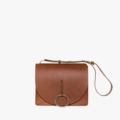 Geometrical shoulder bag in camel chemical-free leather with shoulder strap with silver ringlet that also acts as a closure mechanism