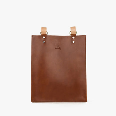 Rectangular minimalist backpack/totebag in camel chemical-free leather with camel strap that can be adjusted through the silver hoops to be worn on the shoulder or as a backpack